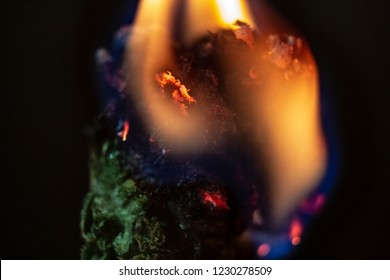 An isolated macro close up of a marijuana bud covered in flame burning away with a black background. Flames surround half of the bud & bright embers burn around the bottom of the flames.