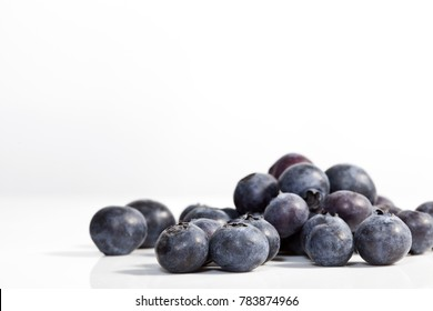 Isolated macro photo of blueberries on white background.  Shallow depth of field with focus on berry.