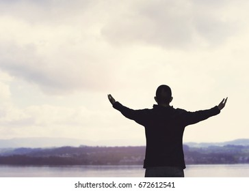 isolated man raise hands up pray for people in the city near wide lake in cloudy day, christian conceptual image of ministry of prayer or world mission