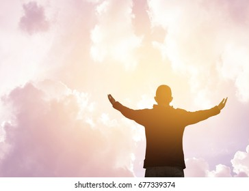 isolated of a man with wide spread arms and hands against cloudy sky and sun light worship and thank God heavenly father, christian worship concept