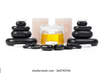 isolated massage stones set with candles and oil; basalt spa stones on white background