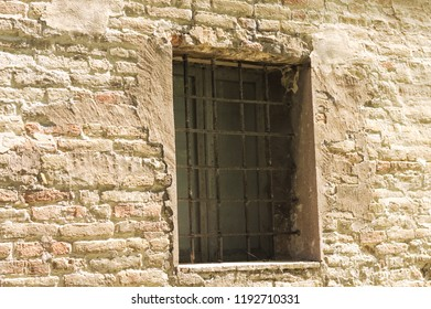 Isolated medieval window with iron gratings (Marche, Italy, Europe)
