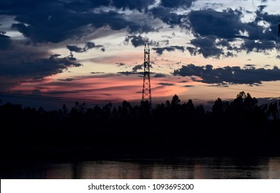 An isolated metallic electric tower with dark cloudy evening sky unique photograph