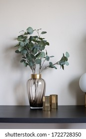 Isolated nice artificial plant in glass vase with gold stainless hexagon vase setting on black wood table / object isolated / interior design