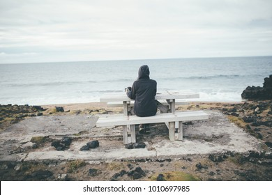 Isolated nostalgic woman siting on a bench by the sea.Pensive female thinking by the calming ocean waves.Pensive person struggling with mental problems,depression and anxiety.Rethinking and reflecting