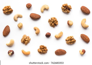 Isolated nuts pattern backdrop. Walnut, cashew, almond and hazelnut  on white background. Top view.