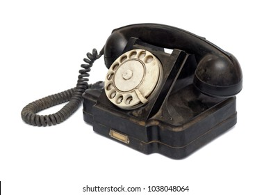 Isolated objects: old black telephone, middle of 20th century, aged and scuffed, isolated on white background. Dust and scratches are kept untouched intentionally.