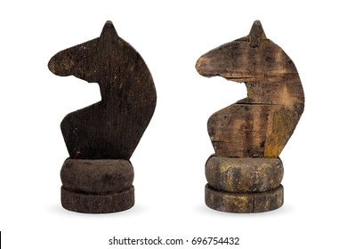 Isolated objects: two very old wooden chess pieces, knights, or horses, black and white