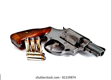 Isolated old revolver handgun with bullets, studio shot
