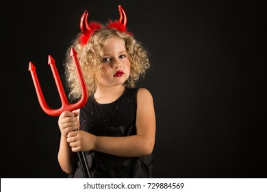 Isolated on black, adorable caucasian blonde little girl in black dress, with red horns on head hold trident