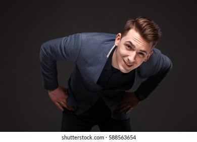 Isolated on black, attractive young caucasian male brunette businessman in grey jacket, costly black watch and black shirt, look at camera, bend forward, hands on waist