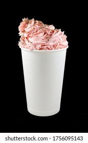 Isolated on a black background, a large white paper Cup with a cold milkshake, decorated with pink whipped cream sprinkled with chocolate chips