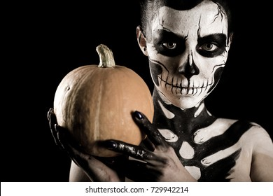 Isolated on black, closeup picture, young brunette caucasian pretty woman with scull body art with a pumpkin in hands, grey eyes, look at camera, wide opened eyes