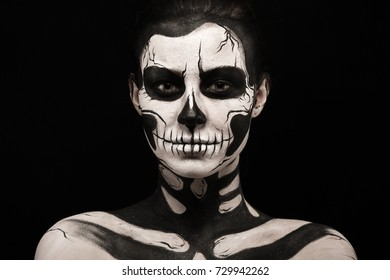 Isolated on black, closeup picture, beautiful young brunette caucasian woman with scull body art, grey eyes, serious
