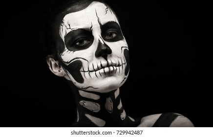 Isolated on black, closeup picture, beautiful young brunette caucasian woman with scull body art, grey eyes, languid look
