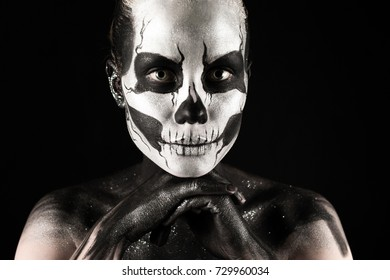 Isolated on black, closeup picture, beautiful young blonde caucasian woman with scull body art, grey eyes, look at camera, languid look