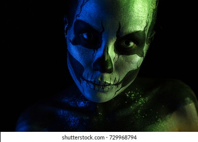 Isolated on black, closeup picture, toned green and blue, beautiful  creepy young blonde caucasian woman with scull body art, grey eyes