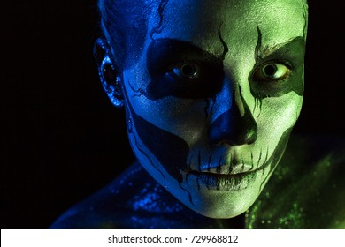 Isolated on black, closeup picture, toned green and blue, beautiful  creepy young blonde caucasian woman with scull body art, grey eyes, languid look