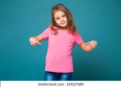 Isolated on blue, adorable caucasian child with long hair, in pink t-shirt and blue jeans, point at herself