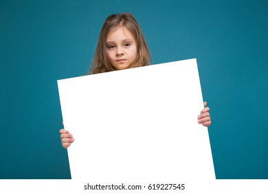 Isolated on blue, attractive caucasian child with long hair, in yellow t-shirt and black trousers hold big empty poster, turned, look at camera