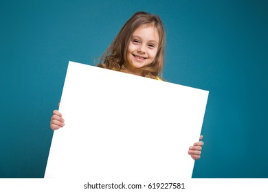 Isolated on blue, attractive caucasian child with long hair, in yellow t-shirt and black trousers hold big empty poster, turned, smiling