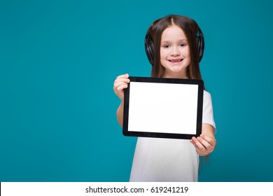 Isolated on blue, attractive caucasian brunette child in white t-shirt, blue jeans and black headphones with long hair show empty tablet, smiling