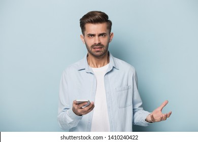 Isolated on blue background angry annoyed man frowns look at camera holding smart phone having problems with wi-fi no wireless connection, need repair broken phone, unpleasant message received concept