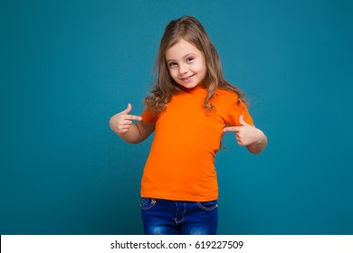 Isolated on blue, beautiful caucasian child with long hair, in orange t-shirt and blue jeans, point at herself, look at camera, glad