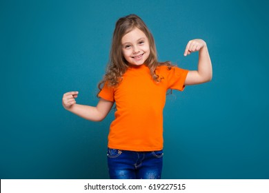 Isolated on blue, beautiful caucasian child with long hair, in orange t-shirt and blue jeans, point at herself