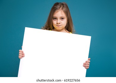 Isolated on blue, beautiful caucasian child with long hair, in yellow t-shirt and black trousers hold big empty poster, turned
