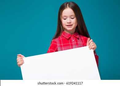 Isolated on blue, beautiful caucasian brunette child in red plaid shirt and blue jeans with long hair hold empty poster, look down
