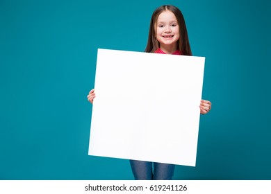 Isolated on blue, beautiful caucasian brunette child in red plaid shirt and blue jeans with long hair hold empty poster, look at camera, stand behind the poster