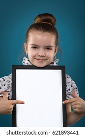 Isolated on blue, beautiful caucasian brunette child hold empty poster, look at camera, stand behind the poster