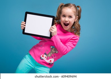 Isolated on blue, beauty cute little caucasian brunette girl in pink shirt with monkey and blue trousers hold empty tablet, bended, blinking, smiling