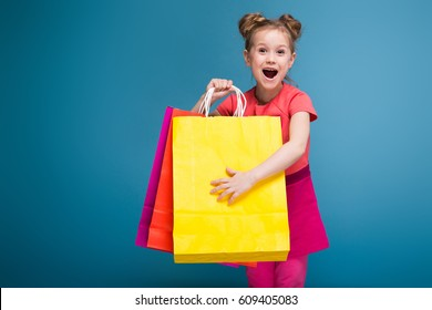 Isolated on blue, cute little caucasian brunette girl in pink dress hold purple, yellow and red paper bags, amazed, look at camera