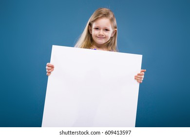 Isolated on blue, cute pretty little caucasian blond girl in purple dress holds big empty poster, look at camera