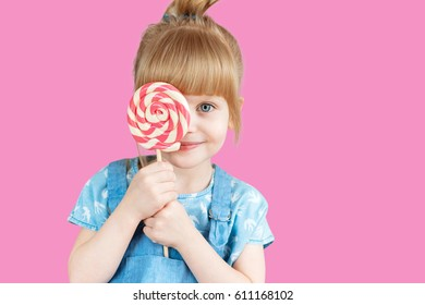 Isolated on bright background, studio. Beautiful little girl with lollipop