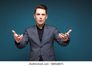 Isolated on dark blue, young handsome caucasian brunette businessman in grey jacket and black shirt shrugs, confused