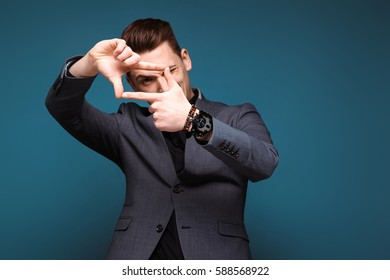 Isolated on dark blue, young handsome caucasian brunette businessman in grey jacket and black shirt looking frame