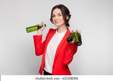 Isolated on grey, beautiful caucasian brunette woman dressed in red jacket and white shirt stand and hold three glass bottles