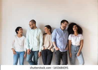 Isolated on grey beige wall five cheerful multi-ethnic friends laughing enjoy live communication together, intimates warm relations, friendship racial equality, like-minded people having fun concept
