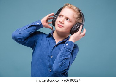 Isolated on grey, teenage blond caucasian boy in blue shirt and black headphones, hands on head
