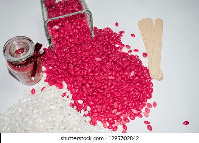 Isolated on a white background is a cool and white granular wax in a glass jar, a red candle and wooden sticks for depilation.