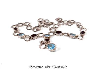 Isolated on white background silver chain with pendants, decorated with topaz and garnets