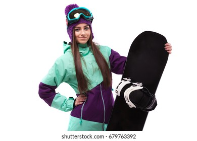 isolated on white, brunette beauty young caucasian girl in purple ski suit and blue ski glasses hold black snowboard, look at camera, hold board with one hand, hand on waist
