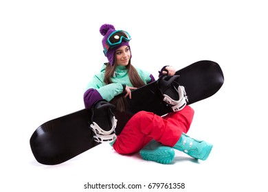 isolated on white, brunette pretty young caucasian woman in purple ski costume, blue snow boots and blue ski glasses siting cross-legged with black snowboard on hands