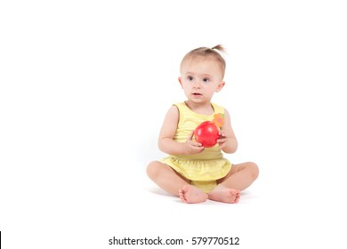 isolated on white, cute happy cheerful caucasian baby girl in yellow dress, hold red apple/ look at camera