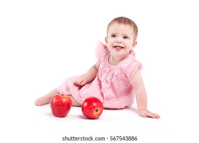 isolated on white, little caucasian girl in pink dress sit with red apples