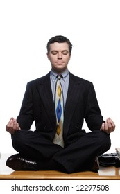 An isolated on white shot of a businessman sitting on desk in a yoga pose.