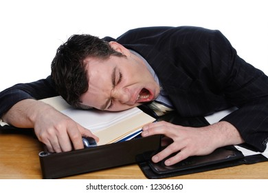 An isolated on white shot of a businessman resting his head on desk yawning.